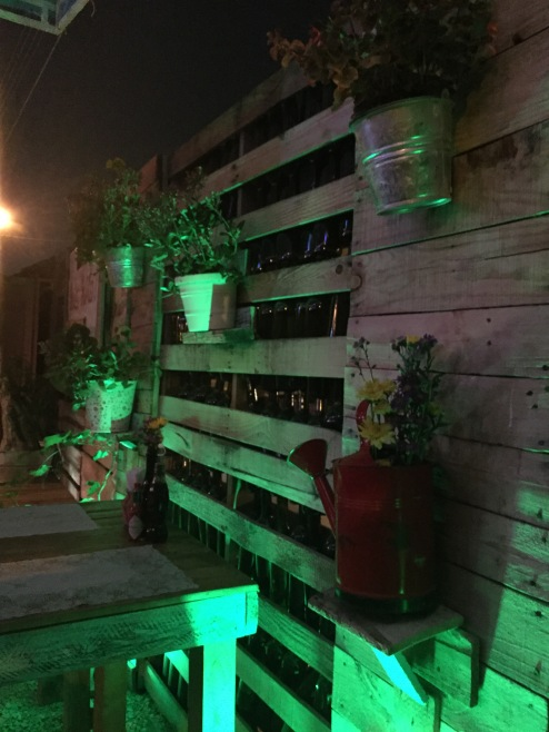 We like this patio wall idea, recycled pallets and beer bottles.
